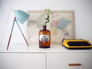 Vintage Sideboard im Esszimmer mit Vintage Tischleuchte, Apothekerflasche, Landkarte und Tippa Reiseschreibmaschine